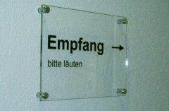 Plexiglas mit Systemtext beschriftet und Abstandshalter an Wand montiert