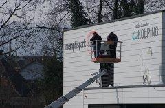 Mit Hilfe einer Schablone Blindschriften auf die Fassade Kleben